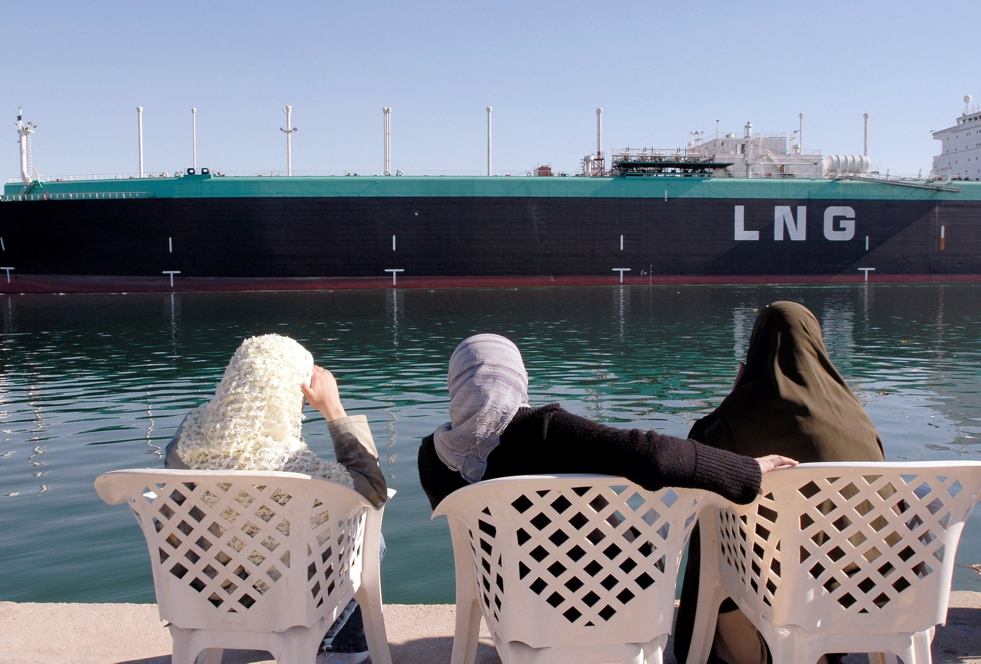Women observe a gas tanker as it sails northbound on the Suez Canal in Ismailia, Egypt.