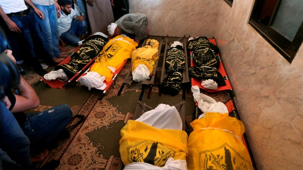 Palestinians mourn over the bodies of members of the same family who were killed overnight in an Israeli airstrike, on November 14, 2019 in Deir al-Bala