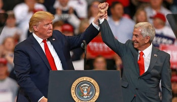 U.S. President Donald Trump speaks with Republican candidate for governor, Eddie Rispone, during a rally in Bossier City, Louisiana on November 14, 2019.