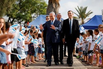 Benjamin Netanyahu walks with Education Minister Rafi Peretz during a ceremony opening the school year in the settlement of Elkana, September 1, 2019