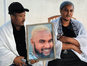 Woreka and Wbjig Teka hold a picture of their son Solomon Tekah, 19, who was killed by an off duty police officer, on July 3, 2019.