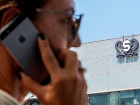 A woman uses her iPhone in front of the building housing the Israeli NSO group, in Herzliya.