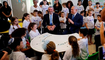 Israeli Prime Minister Benjamin Netanyahu (R) and Education Minister Rafi Peretz attend the opening ceremony of the school year in the Jewish settlement of Elkana in the Israeli-occupied West Bank on September 1, 2019.
