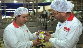 "Workers at the Strauss factory holding ""Milky"" product in Karmiel, in 2018."