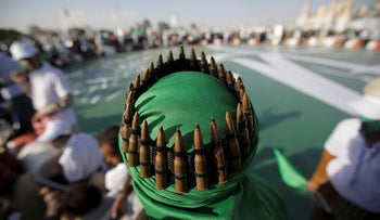 A supporter of Shiite rebels, known as Houthis, with an ammunition belt placed on his head attends a celebration of Moulid al-nabi, the birth of Islam's prophet Muhammad in Sanaa, Yemen