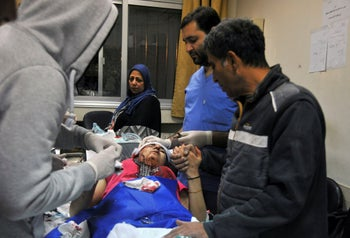 In this photo released by the Syria's SANA news agency, a paramedic treats an injured woman wounded by Israeli missile strikes at a hospital in Damascus, Syria, Wednesday, November 20, 2019.