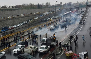 People protest against increased gas price, on a highway in Tehran, Iran, November 16, 2019