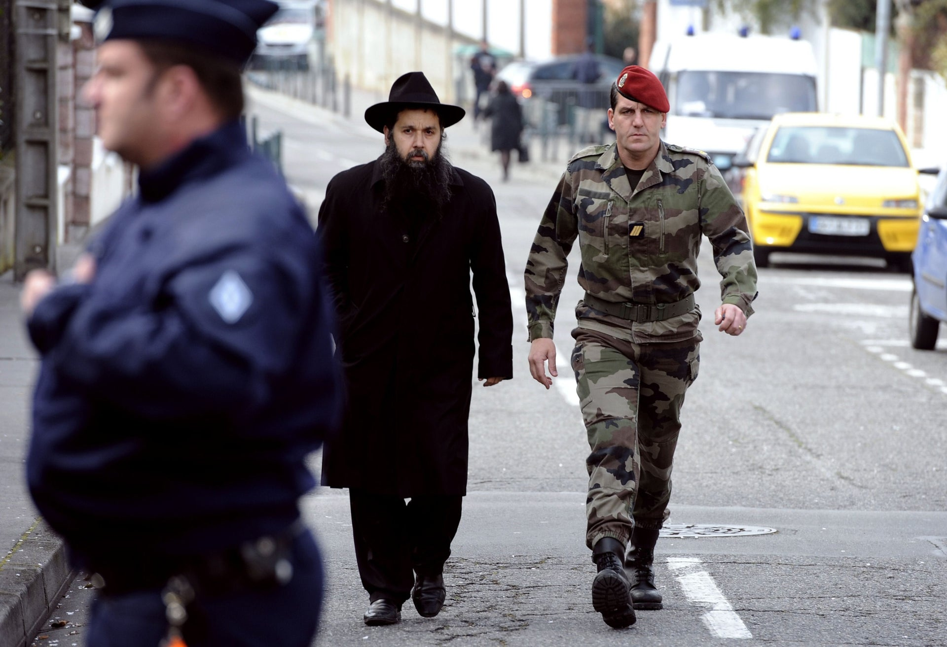 """A rabbi flanked by a French paratrooper leaves the """"Ozar Hatorah"""" Jewish school in Toulouse, a day after the shooting that killed four people there, March 20, 2012."""