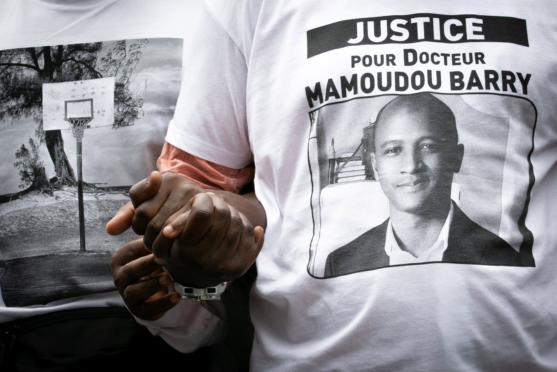 """People wearing shirts reading """"Justice for Dr. Mamoudou Barry"""" hold hands as they take part in a white march in Rouen on July 26, 2019 in hommage to Mamoudou Barry, a young Guinean teacher and researcher killed the previous week after a """"racist"""" assault, according to his family."""
