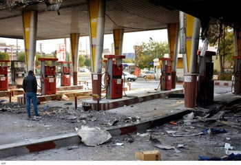An Iranian man checks a scorched gas station that was set ablaze by protesters.