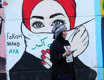 A woman stands in front of graffiti at the Saadoun Tunnel, in Baghdad, November 17, 2019.