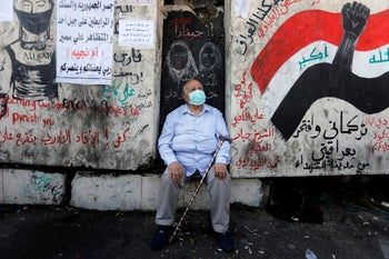 A man sits as he takes part in ongoing anti-government protests in Baghdad, November 21, 2019.