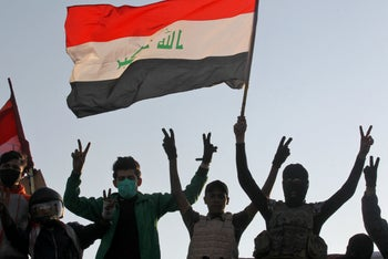 raqi protesters flash the victory sign as they take part in an anti-government demonstration on al-Ahrar bridge in Baghdad on November 19, 2019.