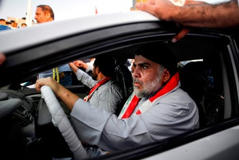 Muqtada al-Sadr drives a car as he joins anti-government demonstrators gathering in the central holy city of Najaf, October 29, 2019.