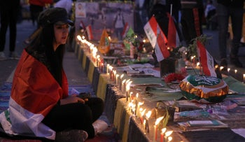 Iraqi anti-government protesters hold a candlelight vigil in Baghdad's Tahrir square on November 21, 2019.