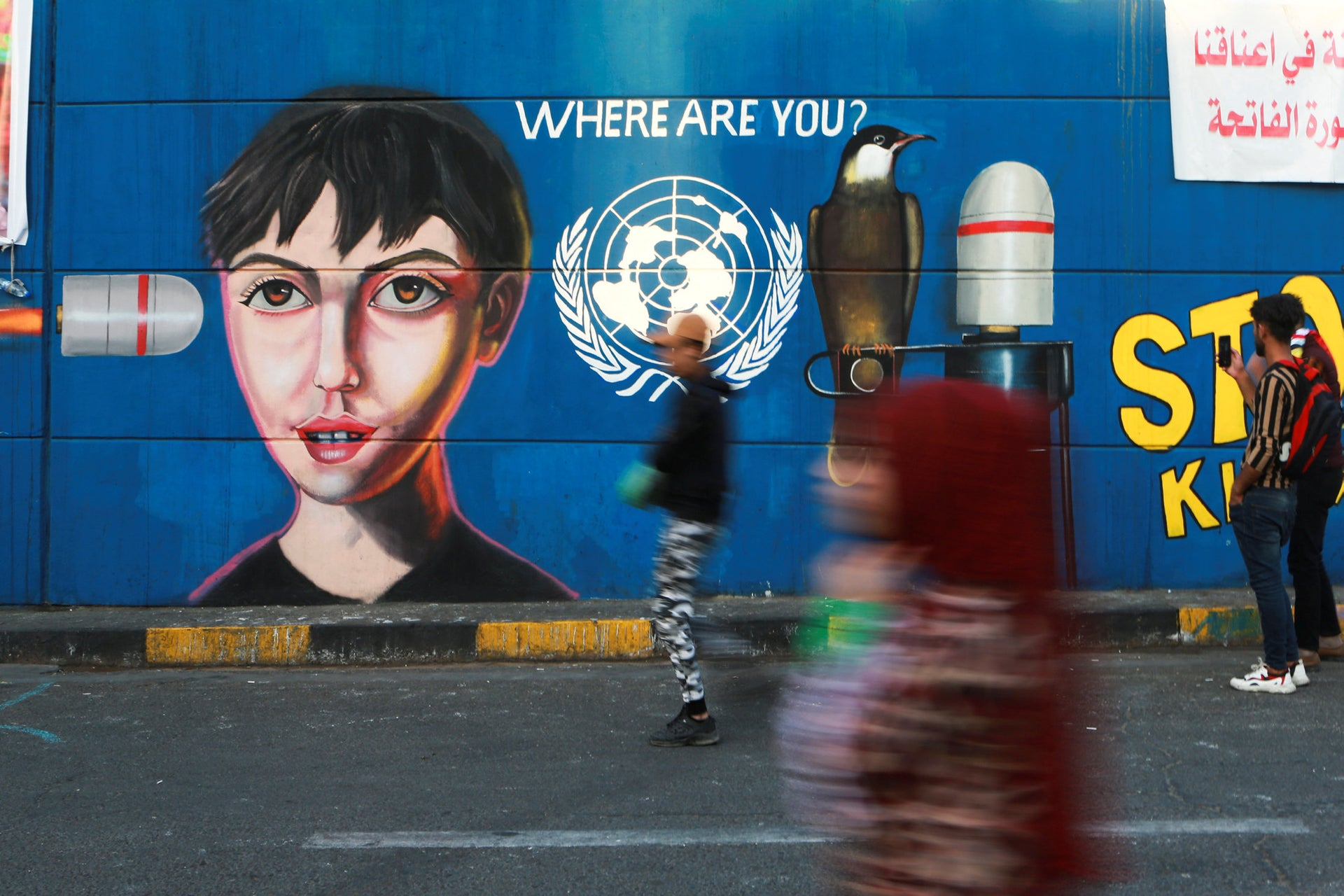 People pass by graffiti at the Saadoun tunnel, in Baghdad, Iraq, November 17, 2019.