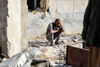 A man crouches as he reacts following a car bomb explosion at the industrial zone in the northern Syrian town of Tal Abyad, on the border with Turkey, on November 23, 2019.