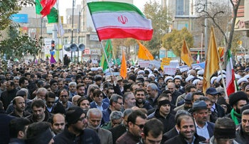 Iranians wave a national flag (R) during a protest, in the northwestern city of Ardabil on November 20, 2019.