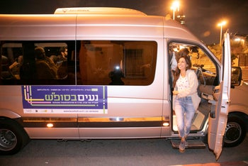 A woman gets off one of the public minibuses that served routes in Tel Aviv on a Shabbat for the first time on November 22, 2019.