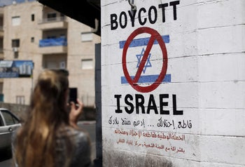 Tourist photographs a sign painted on a wall in Bethlehem, West Bank, June 5, 2015
