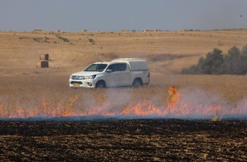 A wheat field hit by an incendiary device launched from Gaza burns near Kibbutz Re'im, on the Gaza border, June 28, 2019.