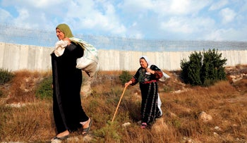 Palestinian women walk along Israel's separation barrier from the Palestinian side near the West Bank village of Dura, October 30, 2019.