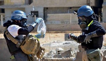 OPCW investigators take samples from sand in the countryside of Ain Terma, Syria, August 28, 2013