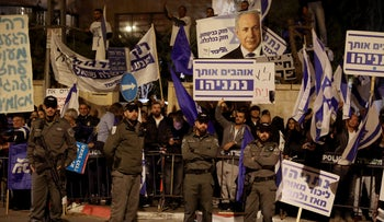 Supporters of Prime Minister Benjamin Netanyahu wave flags and placards as they rally to express their solidarity, outside his Jerusalem office on November 23, 2019.