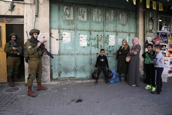 Israel Defense Forces soldiers and Palestinians in Hebron,the West Bank, November 2019.