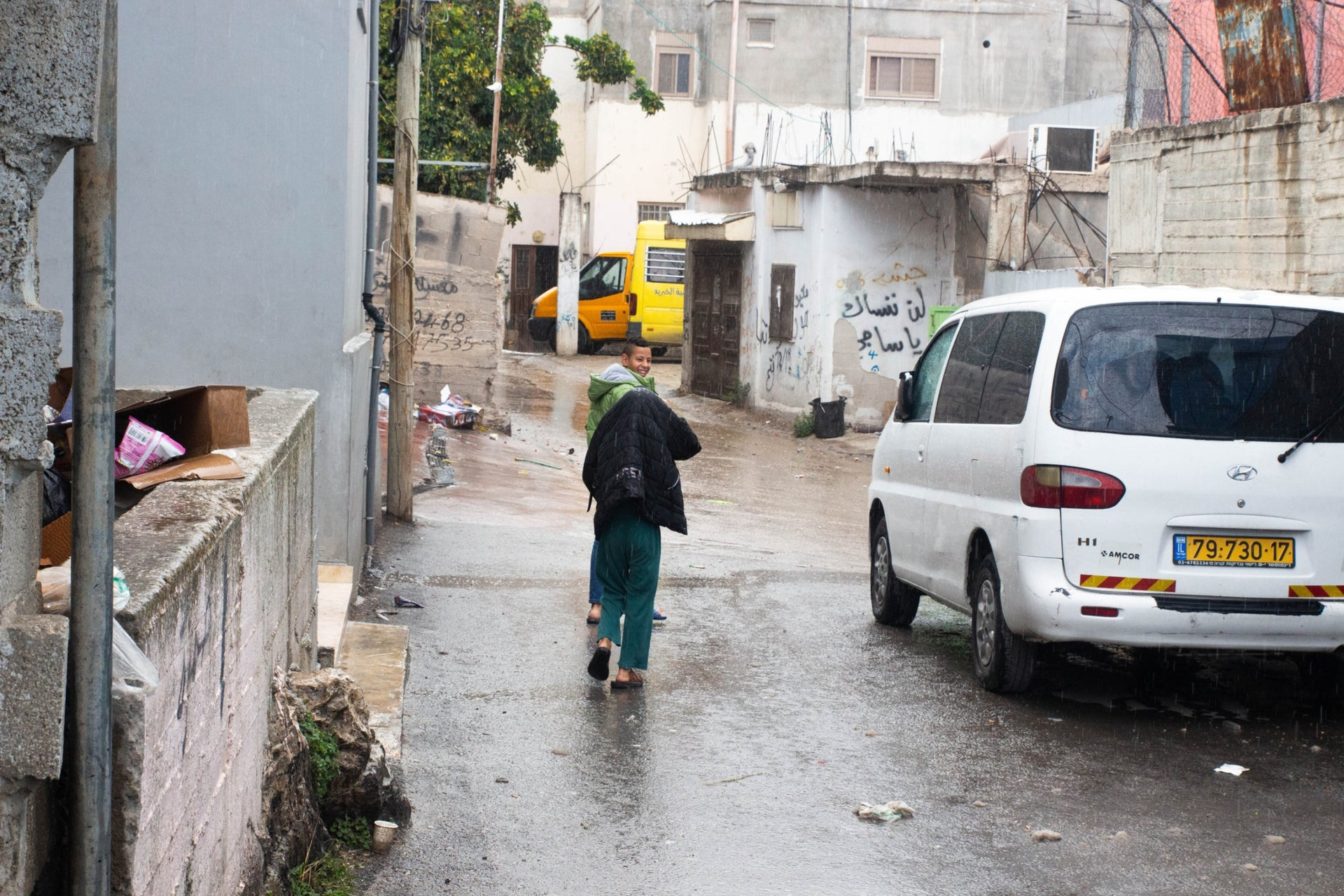 Local children getting caught in a heavy shower on the narrow streets of Deheisheh, near Bethlehem, November 2019.