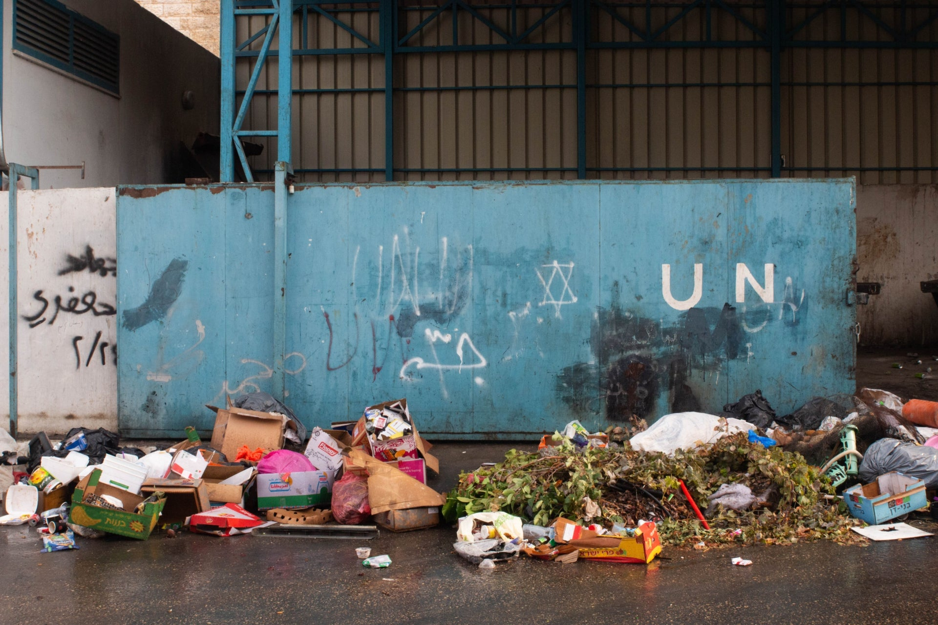The garbage collection point in Deheisheh, organized by the UN Relief and Works Agency. The agency doesn't remove the Star of David graffiti.