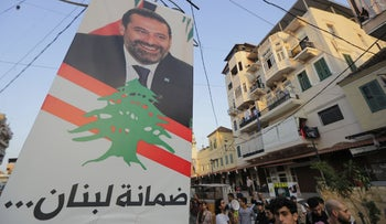 Lebanese protesters get ready to remove the poster of former prime minister Saad Hariri in Lebanon's northern port city of Tripoli on November 7, 2019.