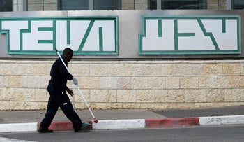A man cleans near the logo of Teva Pharmaceutical Industries at their plant in Jerusalem December 14, 2017.