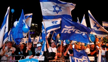 Supporters of Israeli Prime Minister Benjamin Netanyahu chant slogans and hold up signs in support of him during a rally held under the banner in Tel Aviv, November 26, 2019.