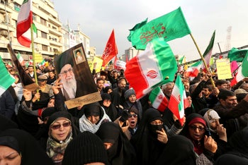 Iranian pro-government demonstrators raise flags and pictures of Supreme Leader Ayatollah Ali Khamenei as they gather in Tehran's central Enghelab Square, November 25, 2019.
