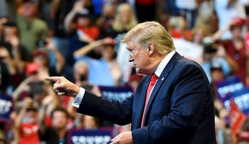 "US President Donald Trump points his finder to supporters during a ""Keep America Great"" campaign rally at the BB&T Center in Sunrise, Florida on November 26, 2019"