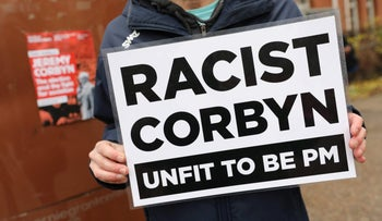 "An anti-Labour activist holding a placard outside the Labour Party's launch of its Race and Faith Manifesto, London, November 26, 2019. The placard says ""Racist Corbyn Unfit to be PM."""