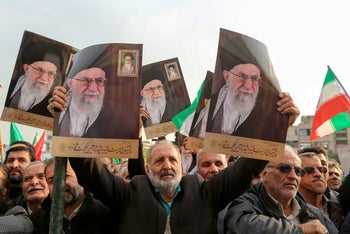 Iranian pro-government demonstrators raise national flags and pictures of Supreme Leader Ali Khamenei in Tehran's central Enghelab Square, November 25, 2019.