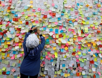 An Iraqi demonstrator pastes a note with her wish at a wall of wishes in Baghdad, November 25, 2019.
