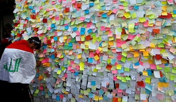 An Iraqi demonstrator pastes a note with his wish at a wall of wishes in Baghdad, November 25, 2019.