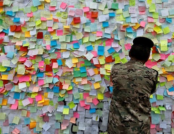 A member of Iraqi security forces pastes a note with his wish at a wall of wishes in Baghdad, November 25, 2019.