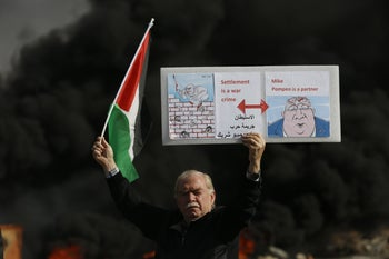 A Palestinian man holding a poster depicting Israeli Prime Minister Benjamin Netanyahu, left, and US Secretary of State Mike Pompeo during a protest against the U.S. announcement that it no longer believes Israeli settlements violate international law., Beit El, November 26, 2019.