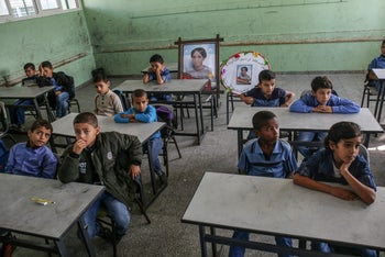 Palestinian pupils with commemorative pictures of their late classmate Moaz Abu Malhous at his school in Deir al-Balah in Gaza, November 16, 2019.