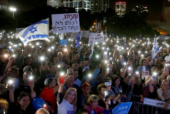 """Supporters of Israeli Prime Minister Benjamin Netanyahu attend a rally held under the slogan """"Protesting the coup."""" The banner reads: """"Netanyahu, you'll never walk alone."""" Tel Aviv, November 26, 2019"""