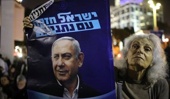 A woman holds a poster that reads, 'Israel is strong with Netanyahu' at the anti-coup protest in Tel Aviv, November 26, 2019.