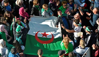 Algerian demonstrators carry a large national flag as they take part in an anti-government protest in the capital Algiers on November 29, 2019.