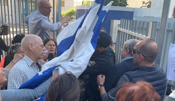 A right-wing activists attempts to strike lawmaker Ahmad Tibi with an Israeli flag, Ramat Hasharon, November 30, 2019.