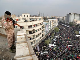 An Iranian soldier stands guard overlooking a pro-government rally organized by authorities in Tehran, Iran, on November 25, 2019.