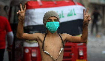 A boy flashes the victory gesture during clashes between anti-government protesters and security forces in Baghdad on November 29, 2019.