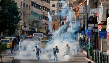 Palestinian youths run from tear gas smoke fired by Israeli security forces on November 26, 2019 during clashes in the West Bank city of Hebron.